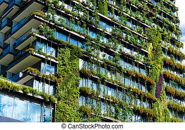 Un rascacielos verde con plantas en la fachada