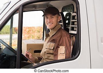 Un repartidor haciendo lista de control en camión