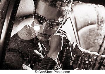 Un retrato blanco de un hombre guapo sentado en el coche