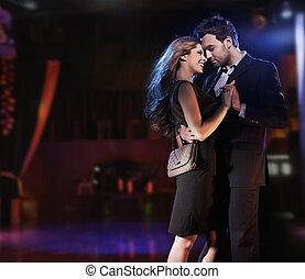 Un retrato conceptivo de una joven pareja con elegantes vestidos de noche bailando