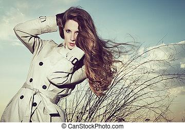 Un retrato de moda de mujer elegante con impermeable en la naturaleza