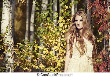Un retrato de moda de una hermosa joven en el bosque de otoño
