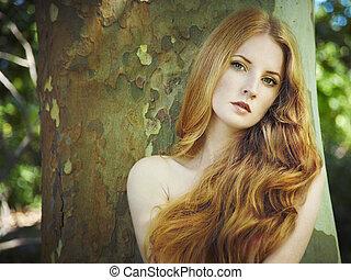 Un retrato de moda de una joven mujer desnuda en el jardín