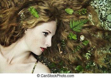 Un retrato de moda de una joven mujer sensual en el jardín