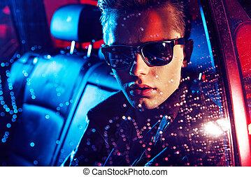 Un retrato de un joven descansando en el coche