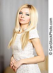 Un retrato encantador de una chica rubia delgada con un vestido claro