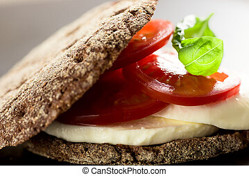 Un sándwich con tomates de mozzarella y pan de centeno