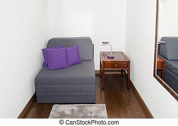 Un sillón gris cómodo con almohada púrpura cerca de una mesa pequeña