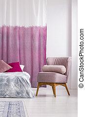 Un sillón rosa en la habitación de la chica