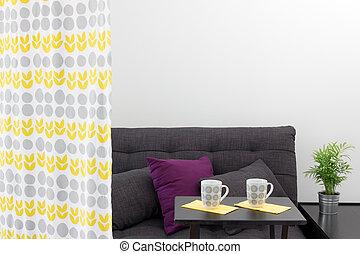Un sofá con cojines detrás de una cortina decorativa