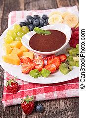 Un surtido de fruta y salsa de chocolate