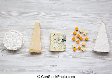 Un surtido de queso diferente en un fondo blanco de madera. Desde arriba, plano.