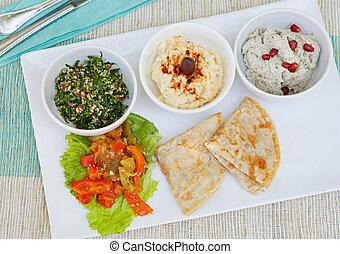 Un surtido de salsas: hummus, garbanzos, ensalada tabbouleh, baba ganoush y pan plano, pita