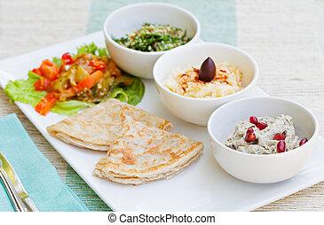 Un surtido de salsas: hummus, garbanzos, ensalada tabbouleh, baba ganoush y pan plano, pita en un plato