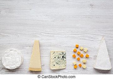 Un surtido de varios quesos en un fondo de madera blanco con espacio de copia. Desde arriba, plano.