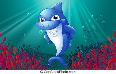 Un tiburón azul sonriendo bajo el mar