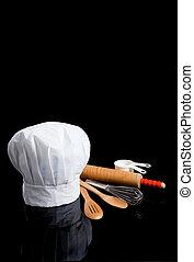Un toque de chef con utensilios de cocina en negro