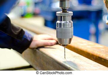 Un trabajador industrial haciendo un agujero con una máquina de perforación automática