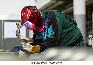 Un trabajador industrial soldado en una fábrica de metal.