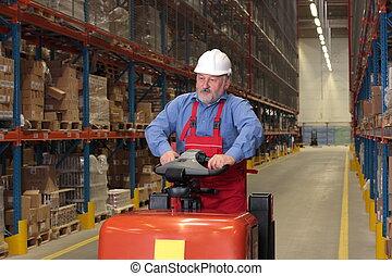 Un trabajador mayor conduciendo el elevador de tenedores