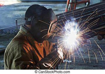 Un trabajador soldado con electrodo de arco eléctrico