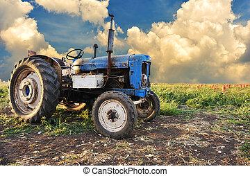 Un tractor muy viejo en el campo, diferentes partes, sin marcas