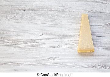 Un trozo de queso parmesano en un fondo blanco de madera. Vista superior, plano, desde arriba. Copia espacio.