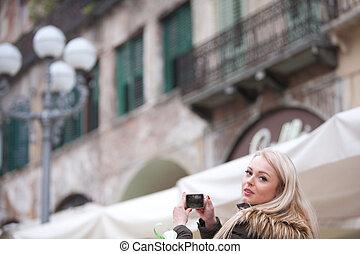 Un turista rubio tomando fotografías en la ciudad