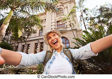 Un turista tomando selfie frente a un edificio histórico