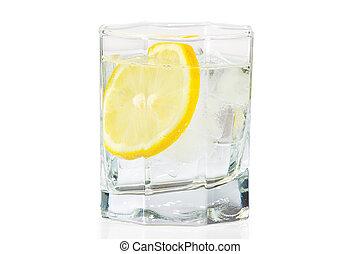 Un vaso de agua, hielo y una rodaja de limón fresco en un fondo blanco