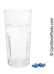 Un vaso de agua y pastillas azules