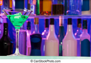 Un vaso de cóctel con alcohol verde en el bar