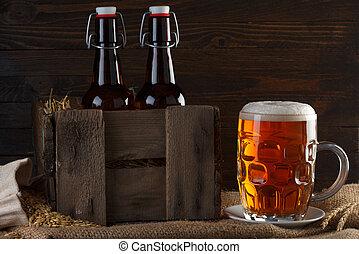 Un vaso de cerveza con botellas de cerveza