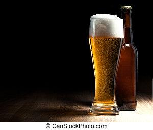Un vaso de cerveza y una botella en una mesa de madera