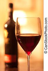 Un vaso de rojo gana con una botella