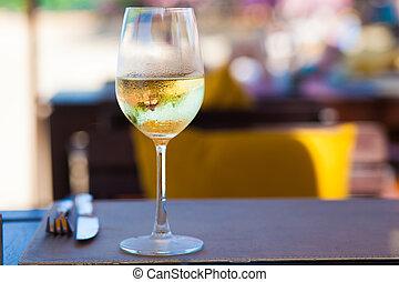 Un vaso de vino blanco frío en la mesa cerca de la playa