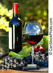 Un vaso de vino tinto con botella y uvas