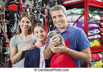 Un vendedor feliz sosteniendo conejo mientras estaba con su familia