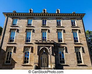 Un viejo edificio de piedra marrón con ventanas azules