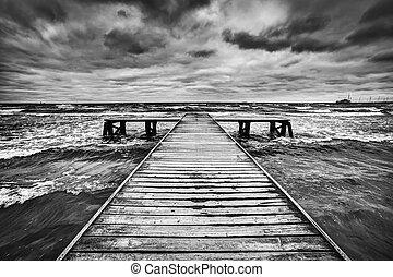 Un viejo embarcadero de madera durante la tormenta en el mar. Cielo dramático con nubes oscuras y pesadas
