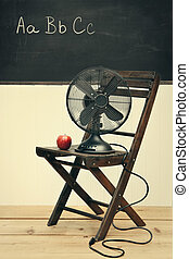 Un viejo fan con manzana en la silla en la habitación de la escuela