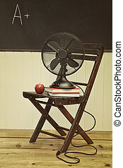 Un viejo fan con manzanas y libros en la silla