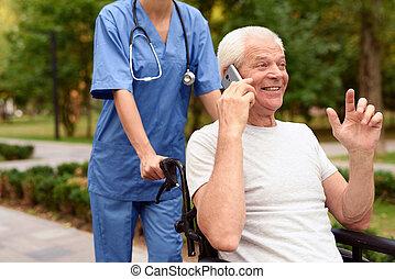 Un viejo feliz en silla de ruedas hablando por teléfono