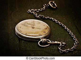 Un viejo reloj con cadenas en la superficie verde