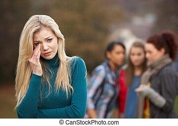 Una adolescente molesta con amigos chismorreando de fondo