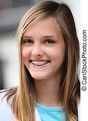 Una adolescente sonriente con aparato dental