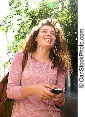Una adolescente sonriente con auriculares afuera