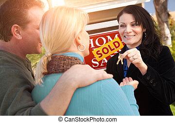 Una agente inmobiliaria hispana entregando nuevas llaves de la casa a una pareja feliz frente a la venta de inmobiliarias