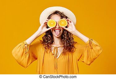 Una alegre y joven mujer rizada con naranja en el fondo amarillo