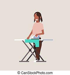 Una ama de casa planchando ropa de mujer afroamericana sosteniendo a una chica sonriente de hierro haciendo dibujos animados femeninos a toda velocidad